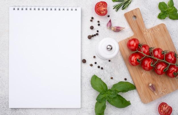 Cuaderno con tomates sobre fondo de madera en la mesa