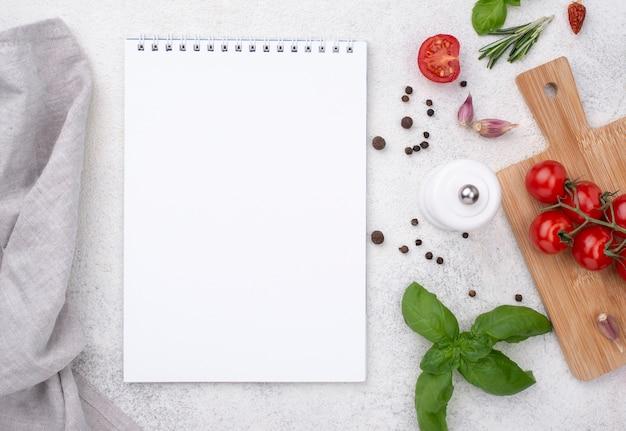 Cuaderno con tomates sobre fondo de madera