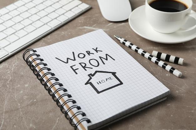 Cuaderno con trabajo desde casa en superficie marrón. lugar de trabajo