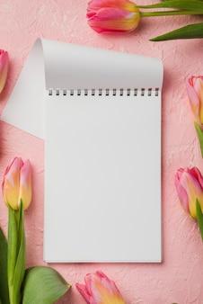 Cuaderno con tulipanes al lado