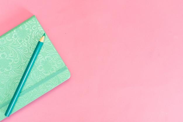 Cuaderno turquesa sobre un fondo rosa y un lápiz