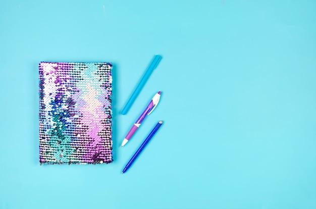 Cuaderno, útiles escolares de color azul y lila sobre fondo azul.