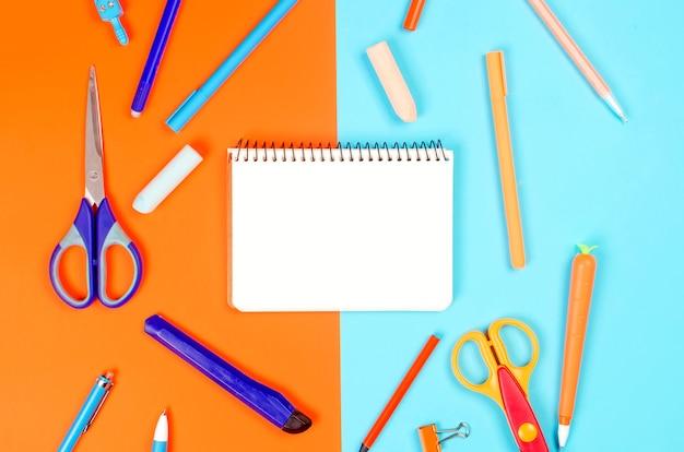 Cuaderno, útiles escolares de color azul y naranja sobre fondo azul.