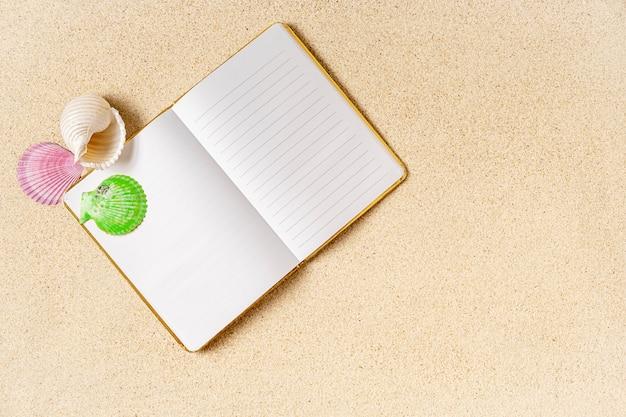 Cuaderno vacío abierto sobre arena con conchas de mar, concepto de verano, espacio de copia,
