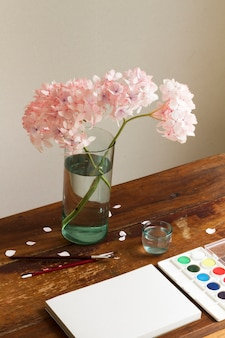Cuaderno vacío con acuarela y flores en un jarrón en el espacio de trabajo de arte