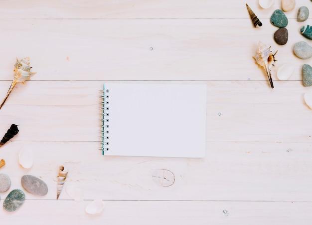 Cuaderno vacío y artículos marinos en superficie rayada