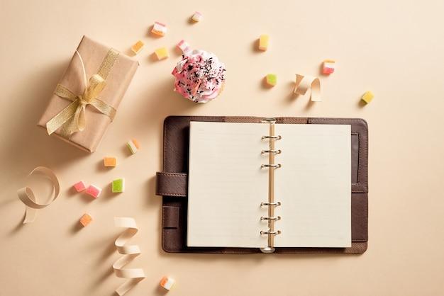 Cuaderno vacío con cajas de regalo y un cupcake con caramelos