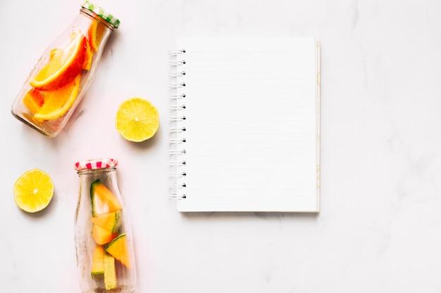 Cuaderno vacío de cal y botellas de vidrio con cítricos cortados.