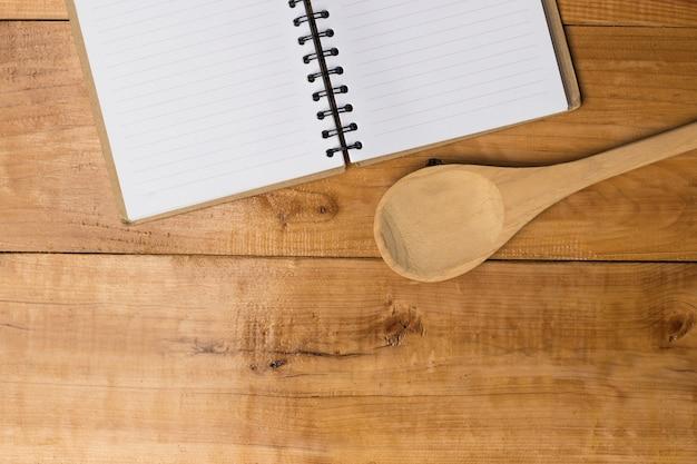 Cuaderno vacío y cuchara en la mesa de madera de color marrón