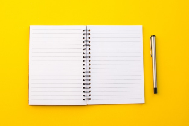 Cuaderno vacío en fondo amarillo con concepto de la escuela.