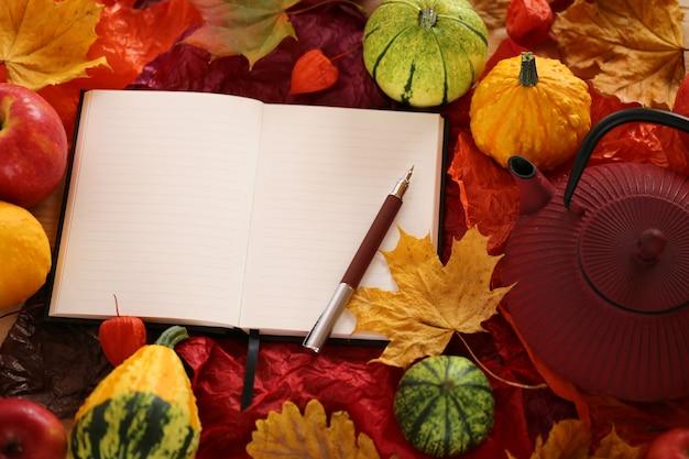 Cuaderno vacío con hojas de arce, manzanas y calabazas