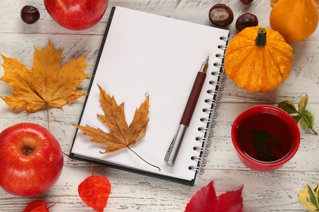 Cuaderno vacío con hojas de arce secas, manzanas, calabaza,