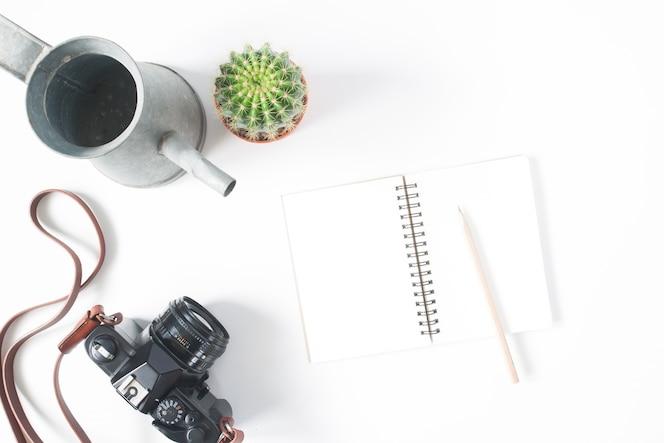 Cuaderno vacío, lápiz, cámara de película, olla de cactus con riego, vista superior, tumbado, aislado en fondo blanco