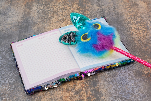 Cuaderno vacío con lápiz sobre espacio de mármol