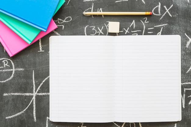 Cuaderno vacío con pluma y libros en la pizarra