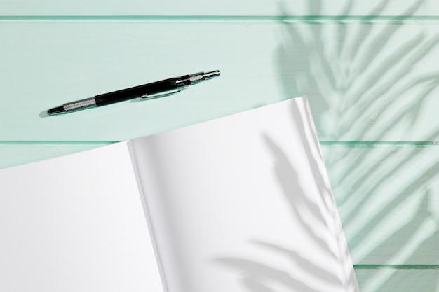 Cuaderno vacío con pluma y sombras