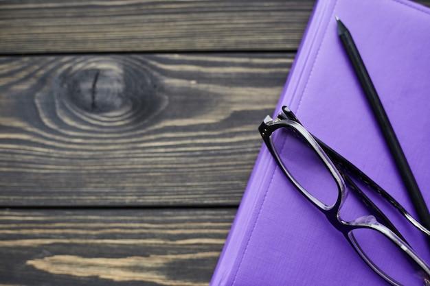 Cuaderno, vasos y lápiz negro sobre mesa de madera rústica