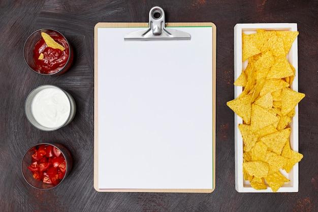 Cuaderno de verduras nachos y salsas blancas en fila