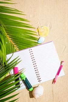 Cuaderno de viajeros con marcadores y bolígrafo sobre arena con fondo de hoja de palmera