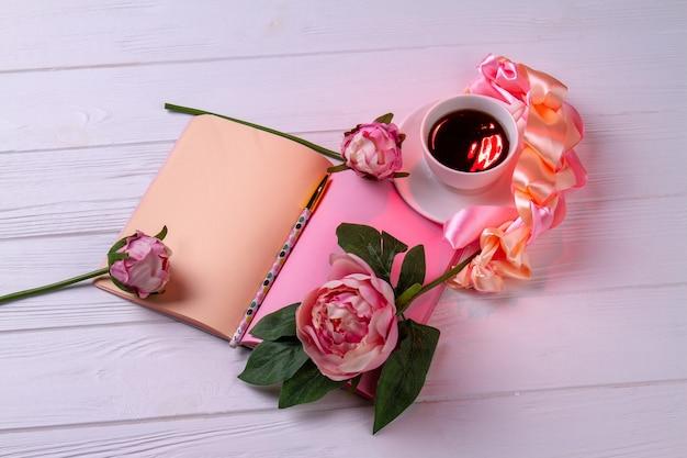 Cuaderno de vista superior con taza de té y flores. fondo de escritorio blanco.