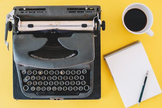 Cuaderno y café cerca de la máquina de escribir
