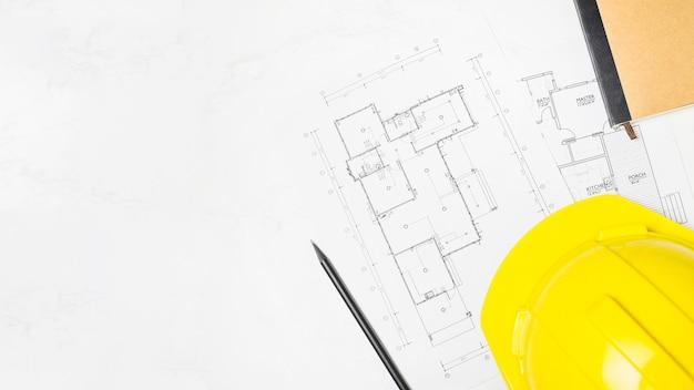 Cuaderno y pluma cerca de proyecto y casco