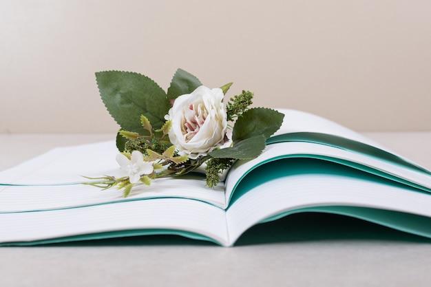 Cuadernos abiertos con falsa rosa sobre fondo beige. foto de alta calidad
