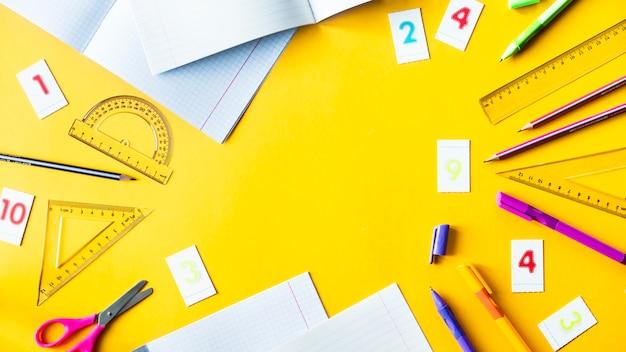 Cuadernos, bolígrafos, lápices, números y reglas sobre un fondo amarillo.