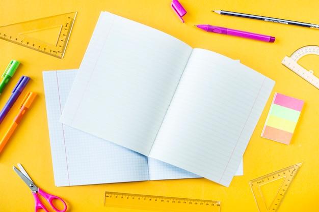 Cuadernos, bolígrafos, lápices y reglas sobre un fondo amarillo.