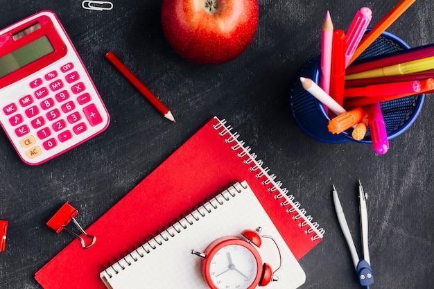 Cuadernos cerca de implementos de oficina y manzana.