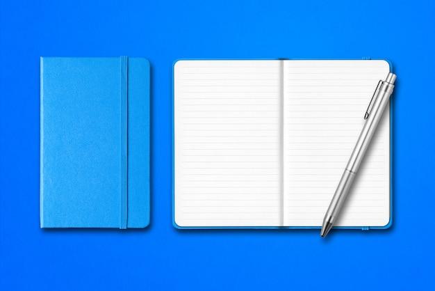 Cuadernos cian cerrados y abiertos con un bolígrafo aislado en superficie azul