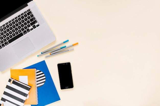 Cuadernos de colores y rotuladores con teléfono móvil y computadora portátil sobre fondo crema