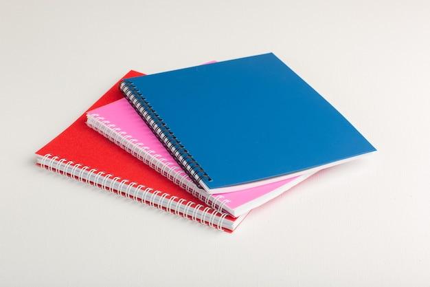 Cuadernos coloridos vista frontal sobre superficie blanca