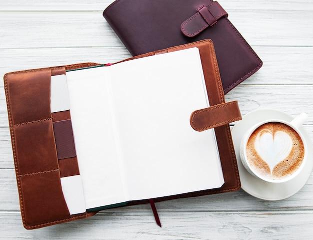 Cuadernos de cuero y taza de café.
