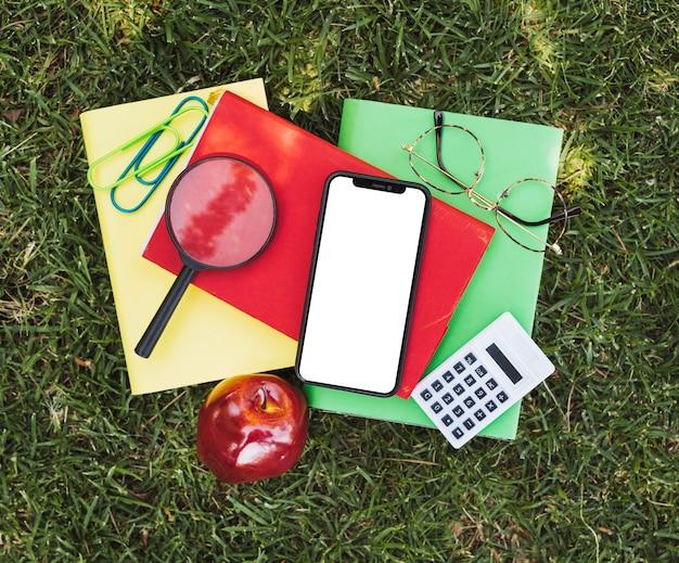 Cuadernos con herramientas ópticas, manzana y dispositivos sobre hierba.