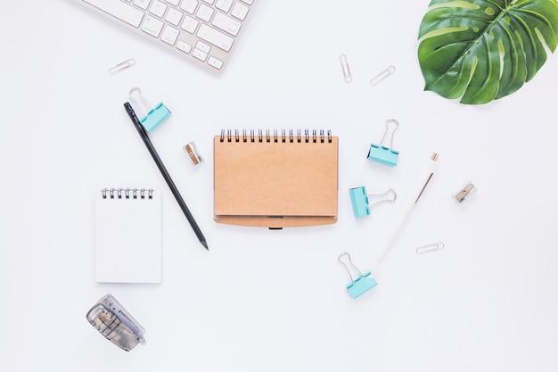 Cuadernos limpios con pequeños estacionarios en el escritorio