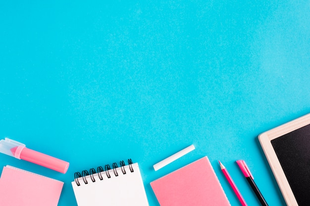 Cuadernos y papelería sobre fondo coloreado.
