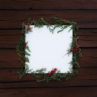 Cuadrado en blanco con pino de navidad hojas alrededor sobre fondo de madera rústica