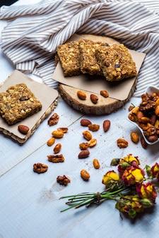 Cuadrados de granola servidos con almendras, nueces y pistachos