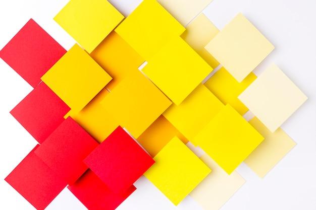 Cuadrados de papel de colores sobre fondo blanco.