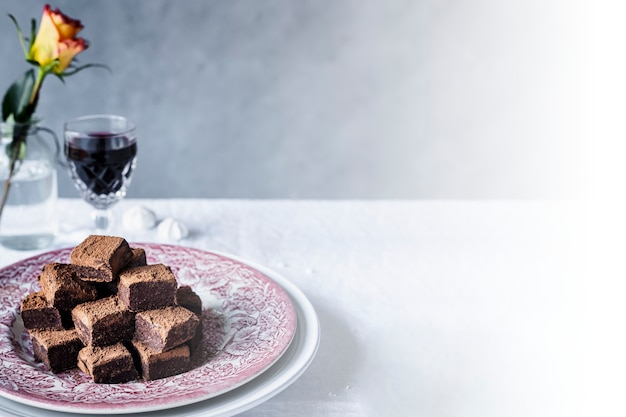 Cuadritos de trufa de ganache de chocolate espolvoreados con cacao en polvo sobre una mesa de comedor