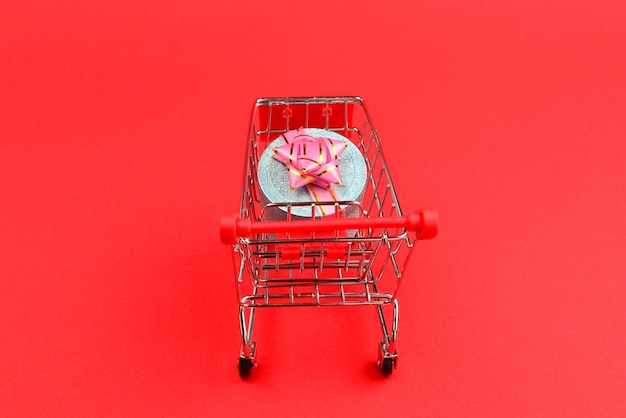 Cuadro actual azul con lazo rosa en un carrito de compras sobre un fondo rojo.