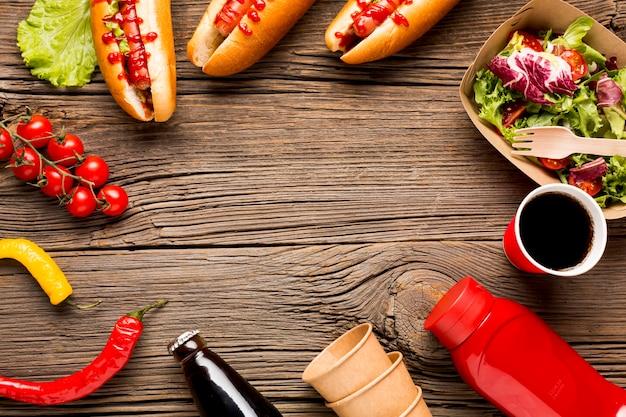 Cuadro de comida con hot dogs y verduras.