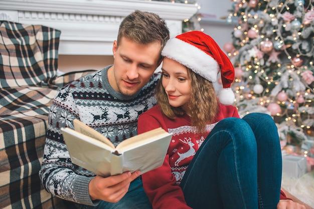 Cuadro del hombre joven y de la mujer que se sientan juntos en piso. ellos leen el libro. lo tiene en las manos. la mujer sonríe un poco. están en habitación decorada.