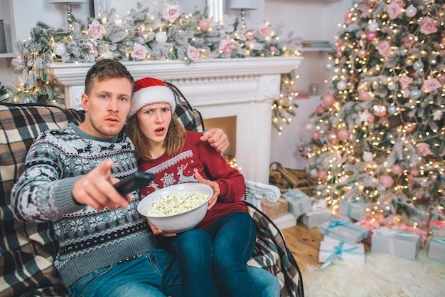 Cuadro del hombre joven y de la mujer que se sientan y que abrazan. están asombrados la gente mira directamente. ella sostiene bownl de palomitas de maíz. el tiene control remoto.