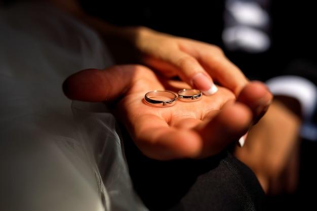 Cuadro del hombre y de la mujer con el anillo de bodas. anillos de novia en la mano del hombre. primer plano de las manos.