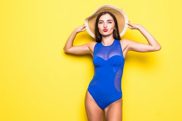 Cuadro de la mujer joven feliz en traje de baño azul aislado sobre la pared amarilla.