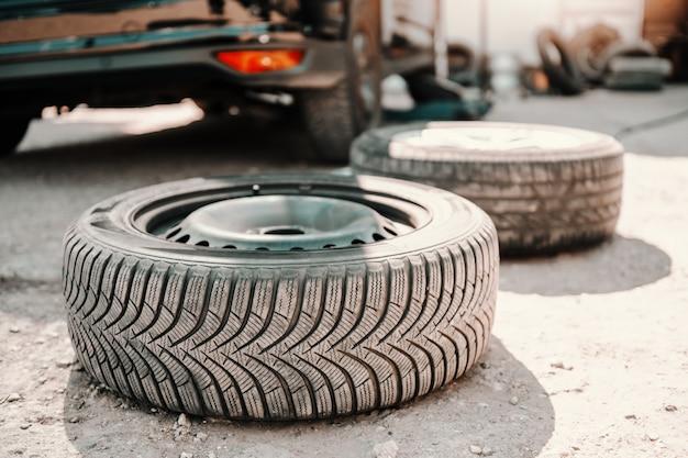Cuadro del neumático viejo en la tierra en el taller del mecánico de automóviles. en coche de fondo.