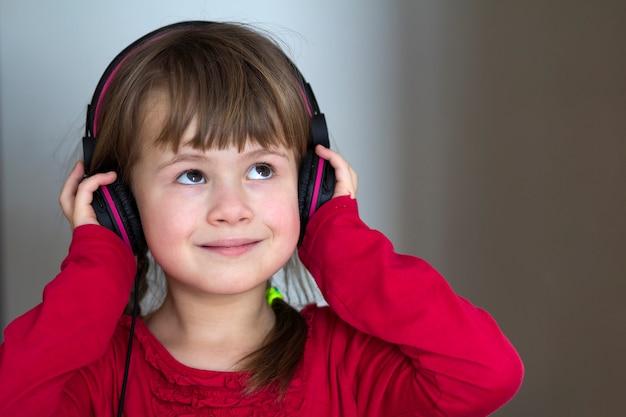 Cuadro de la niña feliz feliz del niño con los auriculares grandes en casa. muchacha alegre del niño que escucha la música en gris borrosa. hogar, tecnología y música.