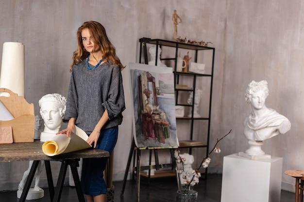 Cuadro de pintura de joven artista femenina en estudio